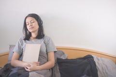 Hörende Musik der schönen Asiatin mit dem Kopfhörer und Ablesenbuch, die auf dem Bett sich entspannen lizenzfreies stockfoto
