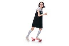 Hörende Musik des asiatischen Mädchens in den Kopfhörern und Fahren auf Skateboard Lizenzfreies Stockbild