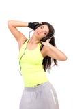 Hörende Musik des jungen Brunette Stockfoto