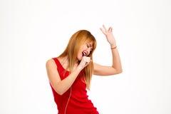 Hörende Musik des jungen schönen Mädchens im headphonesand, das über weißem Hintergrund singt Lizenzfreie Stockfotografie