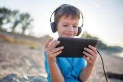 Hörende Musik des kleinen Jungen auf der Tablette im Freien lizenzfreie stockfotografie