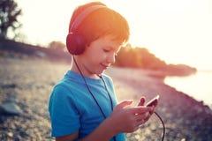 Hörende Musik des kleinen Jungen auf Tablette Sonnenuntergang im im Freien stockfotografie
