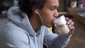 Hörende Musik des Mannes und trinkender Kaffee stock video footage