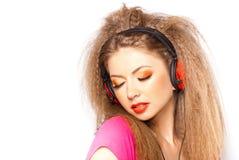 Hörende Musik des netten blonden Mädchens auf großen Kopfhörern Stockbilder