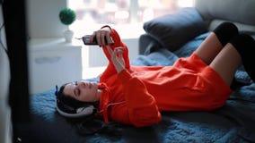 Hörende Musik des netten Mädchens im Sofa der Kopfhörer zu Hause stock footage