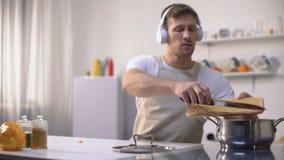 Hörende Musik des positiven Mannes und kochen Gemüse, gesundes kalorienarmes Essen stock footage