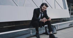 Hörende Musik des recht jungen Mannes mit einem Kopfhörer, der sich neben dem Geschäftszentrum hinsetzt stock video
