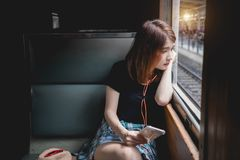 Hörende Musik des weiblichen Passagiers, die mit dem Zug heraus schaut reist lizenzfreies stockbild