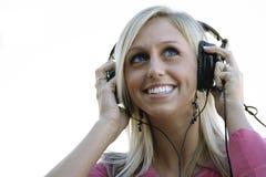 Hörende Musik mit Kopfhörern Stockfotografie