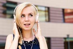 Hörende Musikkopfhörer junger Dame auf dem städtischen Hintergrund, defocused Frau mit glücklichem Gesicht mag Musik Musik und lizenzfreies stockfoto