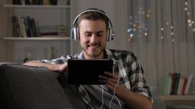 Hörende und aufpassende Videos des glücklichen Mannes auf Tablette