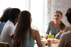 Hörende Unterhaltungslächelnde Frau der gemischtrassigen interessierten Freunde im Café stockfoto