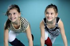 Hörender Erzieher der glücklichen Doppelschwestern Stockfoto