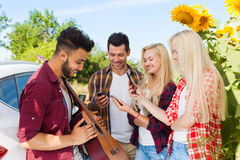 Hörender Kerl der jungen Leute, der die Gitarrenfreunde trinken Landschaft der Bierflaschen im Freien spielt Stockfoto