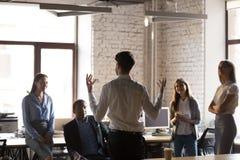 Hörender Teamleiter der verschiedenen Angestellten während der Anweisung lizenzfreie stockfotos