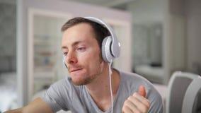 Hörender Ton des Mannes in den Kopfhörern zu Hause stock video