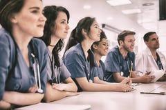 Hörendes Sitzen der Medizinstudenten am Schreibtisch lizenzfreie stockfotografie