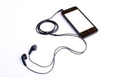 Hörlur och handphone Arkivfoto