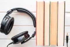 Hörlurar bredvid de gamla böckerna Fotografering för Bildbyråer