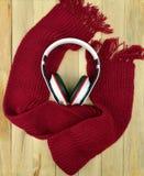 Hörlurar en halsduk på en träbakgrund lyssnar musik till Arkivbilder