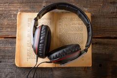 hörlurar för audiobookbokbegrepp Arkivbild