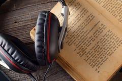 hörlurar för audiobookbokbegrepp Arkivfoto