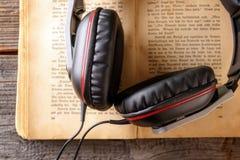 hörlurar för audiobookbokbegrepp arkivfoton