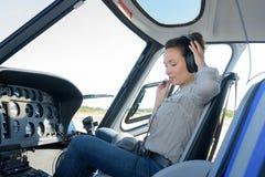 Hörlurar för helikopter för ung kvinna pilot- sättande på huvudet Royaltyfria Foton