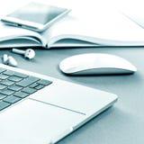Hörlurar för mobiltelefon för anteckningsbok för kontorsskrivbord tonade royaltyfri bild