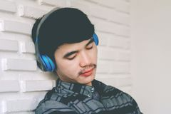 Hörlurar för musik för ung hipsterbög lyssnande Arkivfoton