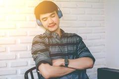 Hörlurar för musik för ung hipsterbög lyssnande Arkivbilder