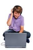 hörlurar isolerade bärbar datorschoolboyen Arkivfoton