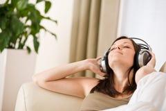 hörlurar lyssnar musik som ler till kvinnan Royaltyfri Fotografi