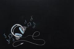 Hörlurar med drog tråd och musikaliska anmärkningar Fotografering för Bildbyråer