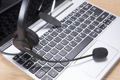 Hörlurar med mikrofon överst av en öppen bärbar datordator fotografering för bildbyråer