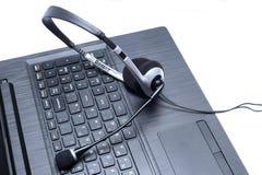 Hörlurar med mikrofon som ligger på ett bärbar datordatortangentbord Royaltyfri Fotografi
