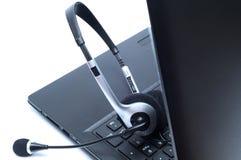 Hörlurar med mikrofon som ligger på ett bärbar datordatortangentbord Arkivfoton