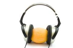 Hörlurar med orange frukt Arkivbild
