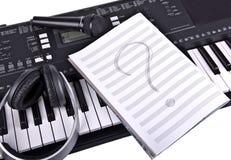 Hörlurar, mikrofon och anteckningsbok på piano Royaltyfri Bild