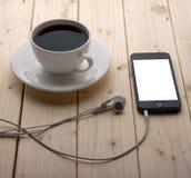 Hörlurar och en kopp kaffe Arkivfoto