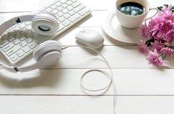 Hörlurar och kaffekoppen på träskrivbordtabellen med rosa färger blommar Musik- och livsstilbegrepp arkivbild