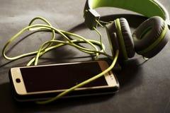 Hörlurar och mobiltelefon arkivbilder