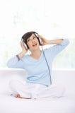 Hörlurar och sjunga för sammanträdekvinna bärande royaltyfri fotografi
