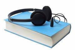 Hörlurar på audiobook Arkivbild