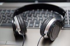 Hörlurar på bärbar datortangentbordet Fotografering för Bildbyråer