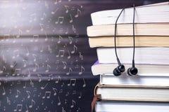 Hörlurar på böcker och flyganmärkningar Begreppet av audiobooks royaltyfri bild