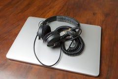 Hörlurar på en bärbar datordator Arkivfoto