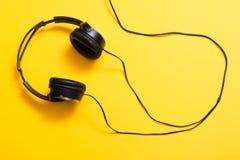 Hörlurar på guling Fotografering för Bildbyråer