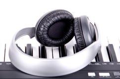 Hörlurar på piano Arkivfoton