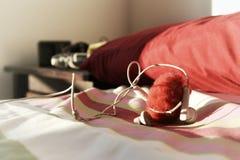 Hörlurar på sängen Royaltyfri Foto
